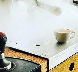 Steaming coffee machine with cappuccino on the side.